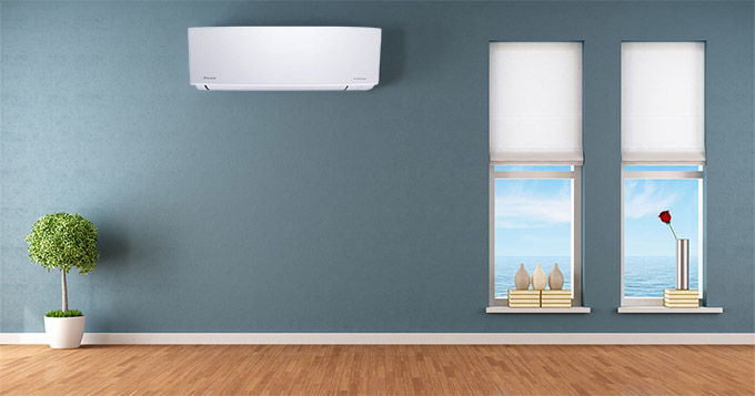 Ductless air conditioning system on a wall next to windows