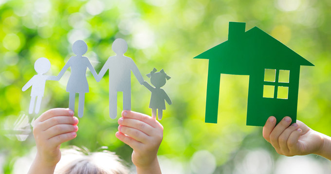 Children holding up paper cutouts of a family and a house symbolizing a healthy, green home
