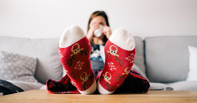 Woman sipping coffee and wearing reindeer socks