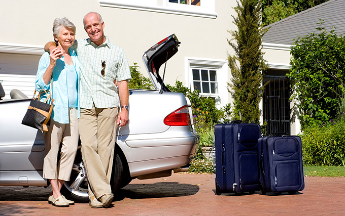 Senior couple next to a convertible with packed suitcases