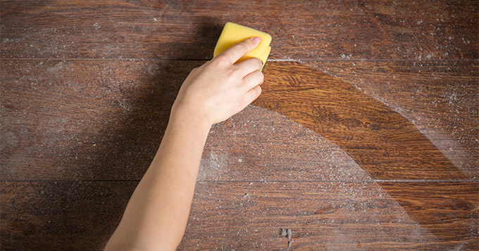 woman's hand wiping away dust with a sponge